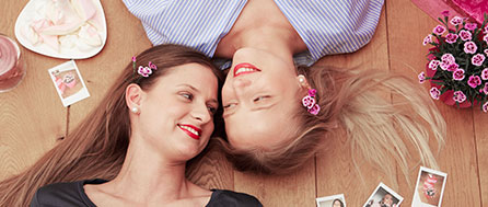 Two friends with Pink Kisses flowers in their hair lying on the floor smiling at each other Description: Pink Kisses® are the perfect gift for your best friend