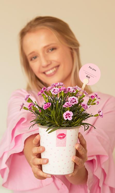 """Eine junge Frau hält dir lächelnd eine Pink Kisses Mininelke im Übertopf mit lauter kleinen rosafarbenen Kussmündern daruaf entgegen. Auf der Rückseite des in der Pflanze steckenden Frienstick-Pflanzensteckers steht """"For you"""". Für eine personalisierte Unterschrift ist eine gestrichelte Linie darunter."""
