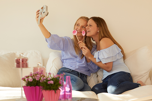 two girl friends sitting on a couch and taking a selfie with an instant camera, holding Pink Kisses Friendsticks in front of their mouth and laughing