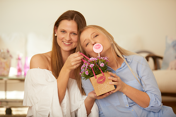 young woman giving her friend a small paper bag with Pink Kisses and a Friendstick