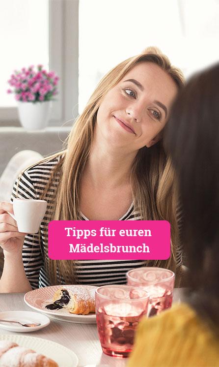 Eine junge Frau sitzt offensichtlich mit ihren Freundinnen am Frühstückstisch, sie lächelt die junge Frau ihr gegenüber an, von der nur ein Teil des Hinterkopfes zu sehen ist. In der Hand hält sie eine Kaffeetasse, vor ihr steht ein Teller mit einem Schoko-Croissant, im Hintergrund ist unscharf eine Pink Kisses Mininelke im Topf audf der Fensterbank zu erkennen.