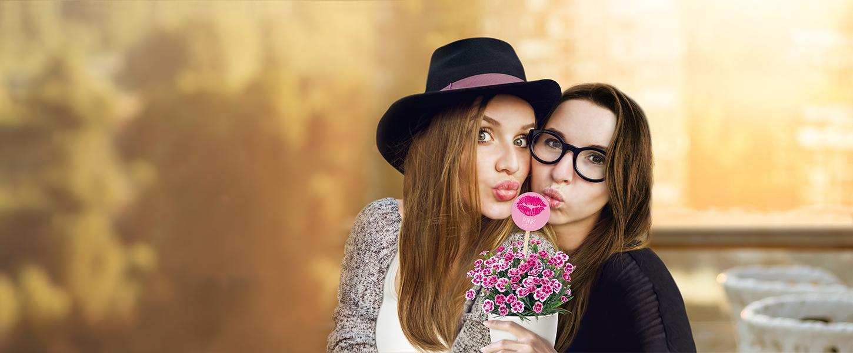 Zwei Freundinnen posieren mit einem Topf Pink Kisses Mininelken und dem Friendstick - einem Stecker mit pinkfarbenem Kussmund darauf - und machen Kussmünder.