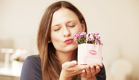 Junge Frau hält eine selbstgestaltete Schmucktüte mit Pink Kisses Mininelken darin in die Kamera und macht einen Kussmund.