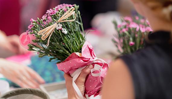 Pink Kisses in selbstgemachter Geschenkverpackung mit rosafarbenem Papier und Schleife auf Stroh