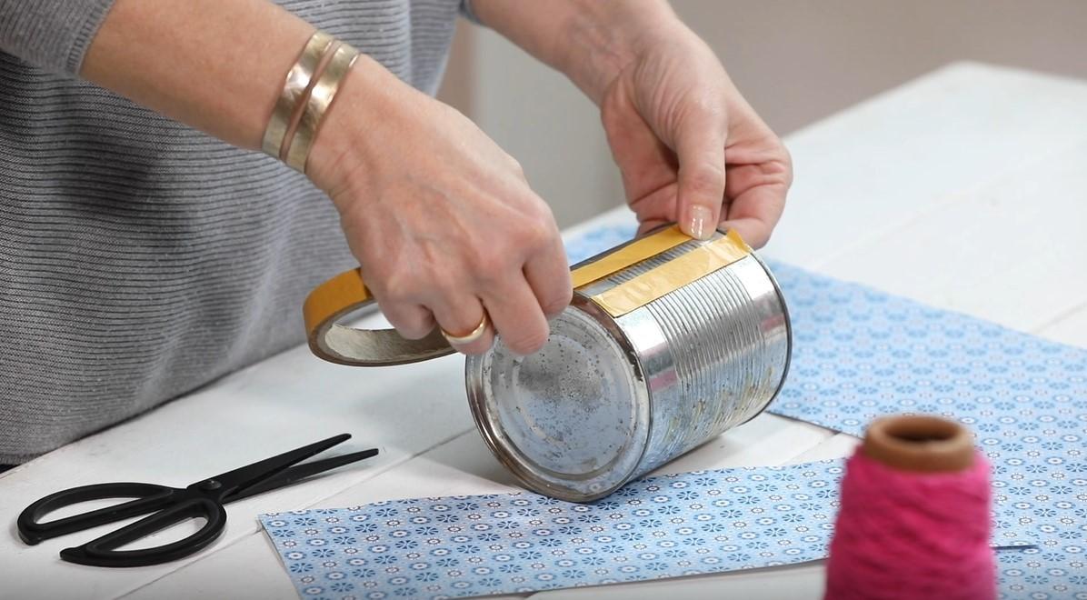 Doppelseitiges Klebeband wird senkrecht auf die Konservendose geklebt.
