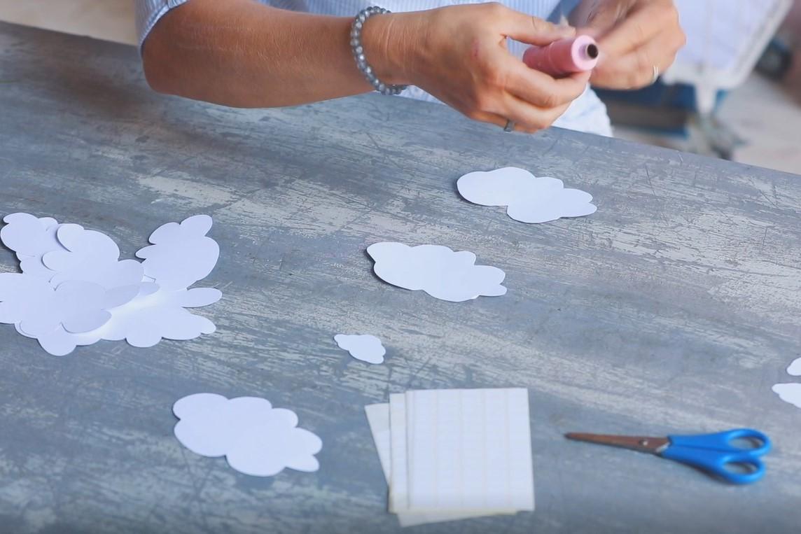 Aus Papier geschnittene Wolken werden mit einem Bindfaden verbunden