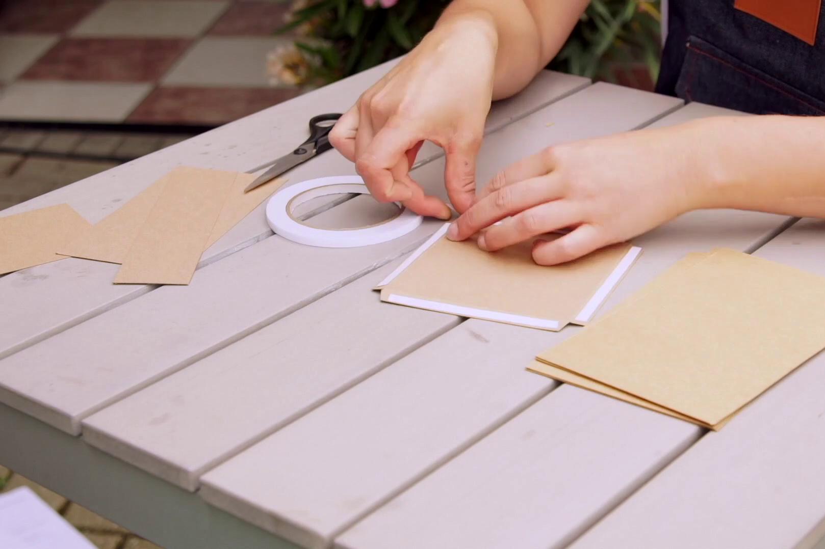 Doppelseitiges Klebeband wird für die Klebeblaschen angebracht